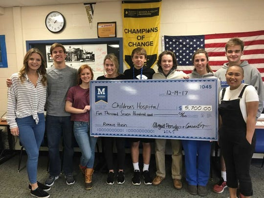 Students present a $5,700 check to Madeira alum Ronnie