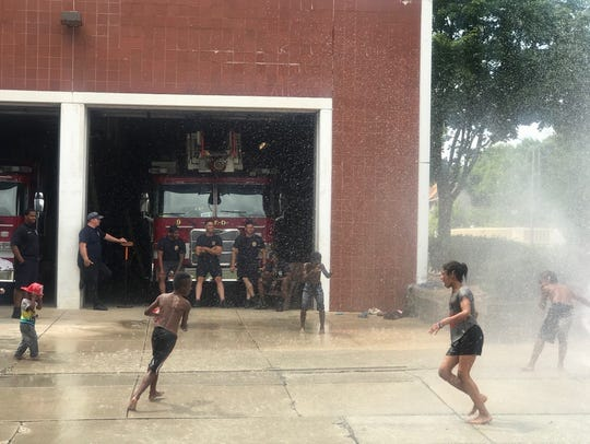 Firefighters from Station 32 watch on with wide grins as local kids have a blast.