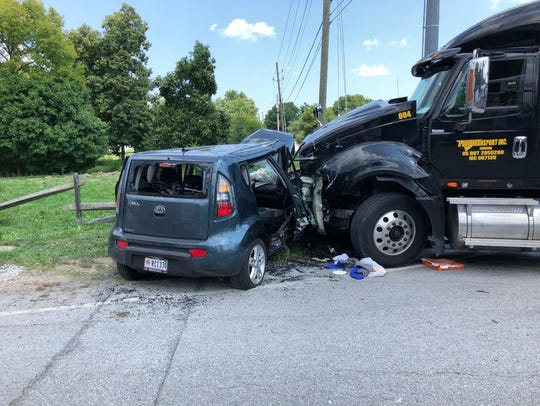 A semi truck and car crash in head-on collision, sending