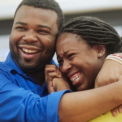 Michigan Technical Academy third-grade teacher Andrew Knox comforts first-grade teacher Alexis Jackson as she is overcome with joy after an announcement that their requests for help with school supplies was granted by DonorsChoose.org on Tuesday.