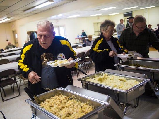 Raymund Kump, of Biglerville, adds pork and sauerkraut