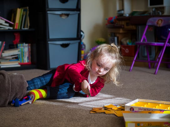 Alaina Crone, 3, plays a card game on the living room