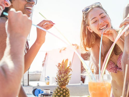 Happy friends drinking tropical cocktail in boat party outdoor - Young people having fun on summer vacation - Youth lifestyle, friendship,  travel and holidays concept - Focus on right girl face