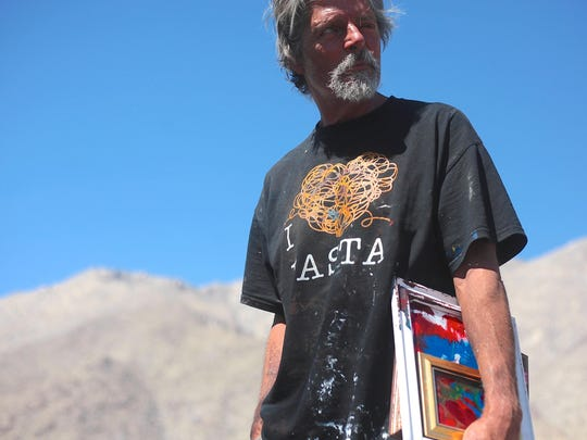 Robert Staich, 63, a local street artist carries his original abstract 'smush' paintings while drifting through the Palm Springs area on June 1, 2015.
