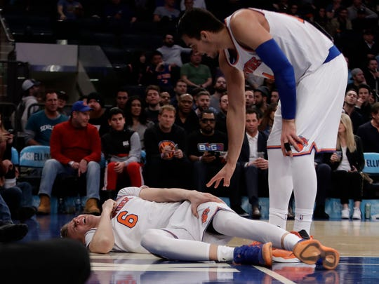 Knicks' Kristaps Porzingis reacts after being injured as Willy Hernangomez, right, checks on him during the second half of a game Tuesday, March 14, 2017, in New York. The Knicks won 87-81.