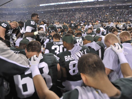 Chris Norman leads the Spartans in a prayer at midfield as MSU beats TCU, 17-16, in the Buffalo Wild Wings Bowl in December 2012.