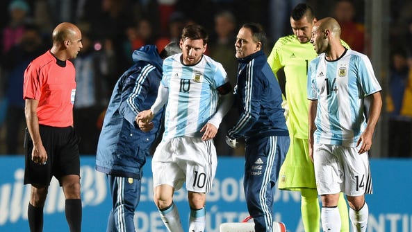 Argentina forward Lionel Messi (C) is assisted after
