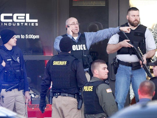 Police guard the front door of Excel Industries in Hesston, Kan., Thursday, Feb. 25, 2016, where a gunman killed an undetermined number of people and injured many more.