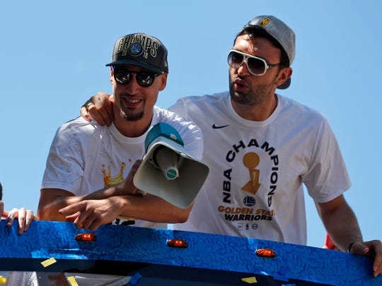 Warriors' Klay Thompson, left, and Zaza Pachulia ride together during the team's NBA championship parade June 12, 2018, in Oakland.