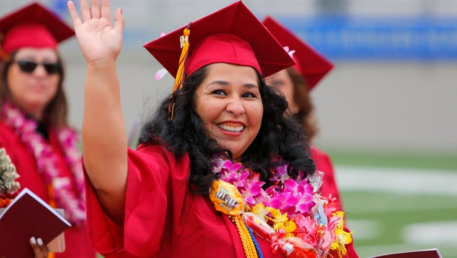 Cindy Elizalde waves to the crowd during the Hartnell College 2015 Commencement on Thursday, May 28, 2015 at Rabobank Stadium in Salinas.