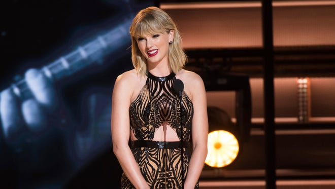 Taylor Swift presents the award for entertainer of the year at the 50th annual CMA Awards at the Bridgestone Arena on Wednesday, Nov. 2, 2016, in Nashville, Tenn. (Photo by Charles Sykes/Invision/AP)