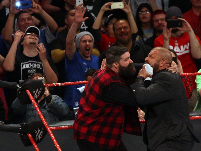 "Mick Foley, left, puts ""Mr. Socko"" on Triple H as the"