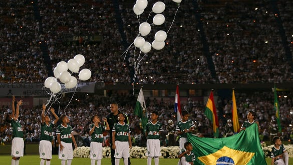 Children release balloons during a tribute to members