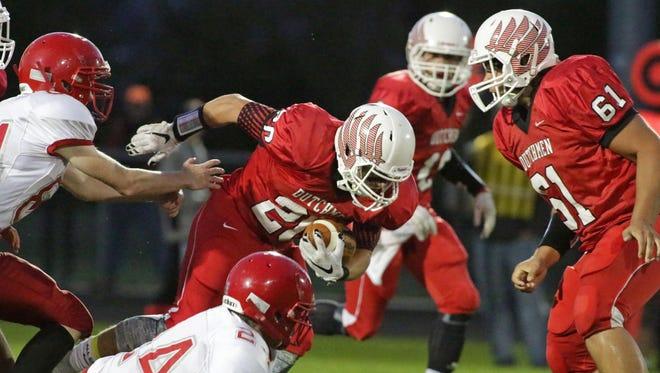Oostburg's Brody Gatz (20) battles in his run for a touchdown against Manitowoc Lutheran Friday at Oostburg.