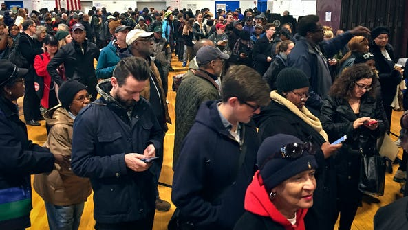 Voters line up in crowds at a polling site to cast