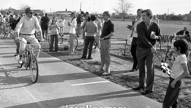 Journal & Courier city editor Bob Kriebel, riding in tandem wth wife Nancy, gets the checkered flag from Lafayette mayor James Riehle at the first annual Jeff '100' bike race at the Jefferson High School track. Photo taken May 4, 1974.