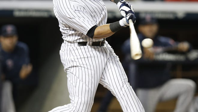 The Yankees' Carlos Beltran hits a seventh-inning double against the Red Sox Sunday night at Yankee Stadium. Beltran also hit a two-run homer in the game and played first base for the first time in his career after Francisco Cervilli got hurt.
