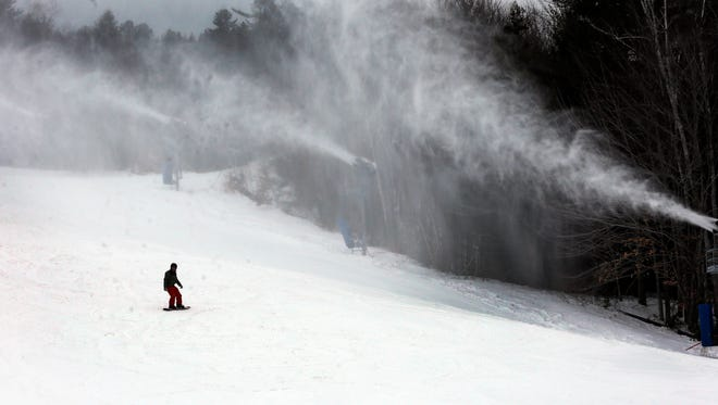 FILE - In this Jan. 15, 2016, file photo, a snowboarder makes his way down the mountain at Attitash ski area in Bartlett, N.H. Skiing is an expensive sport but there are ways to save money thanks to discount ticket websites, Learn to Ski and Snowboard Month and Bring A Friend programs.