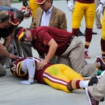 Washington Redskins quarterback Robert Griffin III (10) is attended to on the sideline after injuring his left ankle during the first half of an NFL football game against the Jacksonville Jaguars, Sunday, Sept. 14, 2014, in Landover, Md.