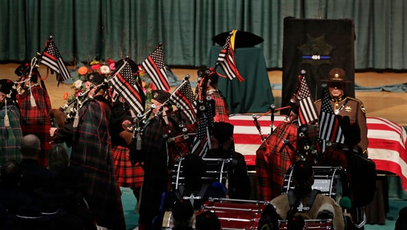 Pipe band members carrying flags march past the casket
