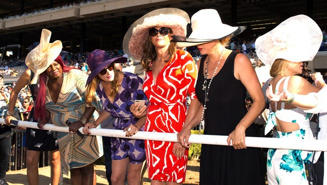 In a photo provided by Benoit Photo, Caitlyn Jenner, center, and friends are trackside to watch the seventh race Thursday, July 16, 2015 as the Del Mar Thoroughbred Club opened is annual summer meet in Del Mar, Calif. (Benoit Photo via AP)