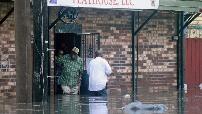 Patrons emerge from a flooded club on Orleans Avenue after a torrential downpour flooded New Orleans streets Saturday, Aug. 5, 2017. Officials in New Orleans say heavy rainfall overwhelmed the city's pump stations, contributing to flooding in some areas.