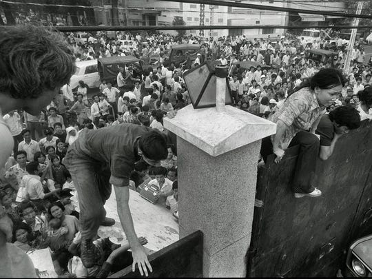 South Vietnamese civilians scale the 14-foot wall of