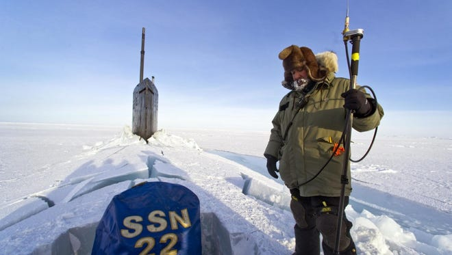 Hector Castillo watches daily operations while communicating with the command hut at the Applied Physics Lab Ice Station as the Seawolf-class attack submarine USS Connecticut prepares to submerge under the ice during ICEX 2011.