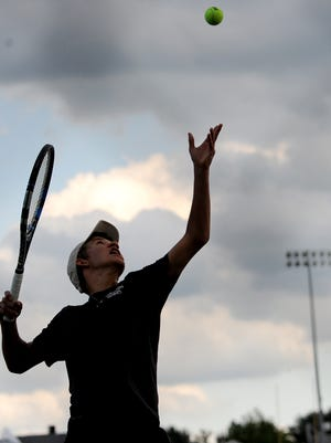 Lexington's Josh Mueller serves during Tuesday's doubles match with Christian Zupan against Ottawa Hills.