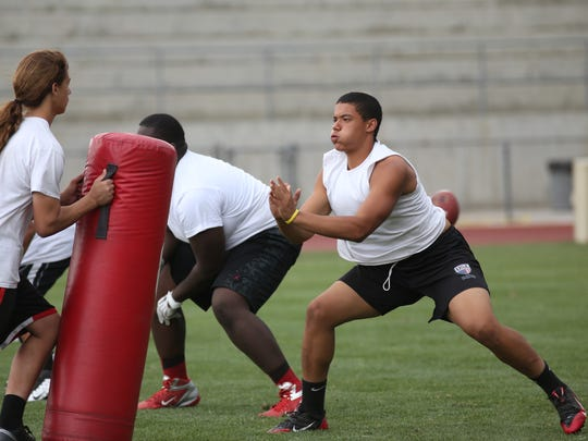 Tyler Hawkins works on his blocking skills during a summer practice at Palm Springs High School.