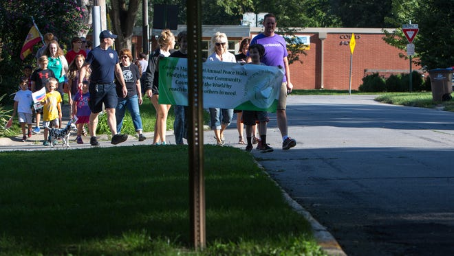 """Cowles Montessori students and families walk from the sidewalk to the street Friday, Sept. 2, 2016, as they participate in their annual school-wide """"Peace Walk"""" at the school in Windsor Heights."""