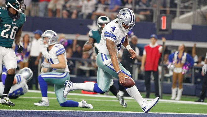 Dallas Cowboys quarterback Dak Prescott (4) runs for a 7-yard touchdown in the first quarter against the Philadelphia Eagles at AT&T Stadium.