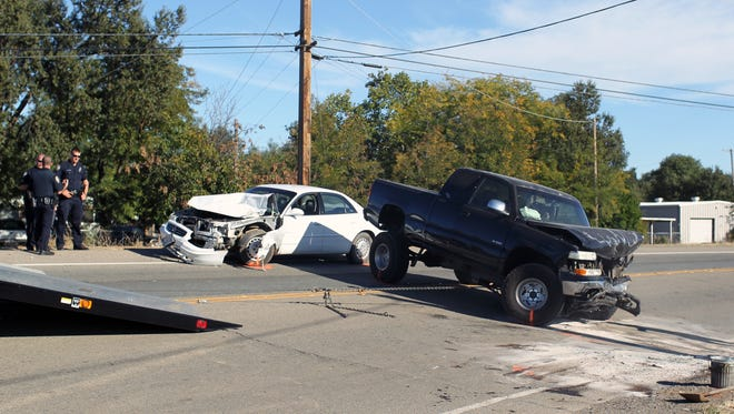 Redding police officers, left, investigate a three-vehicle collision that closed Airport Road on Wednesday afternoon.