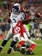 Arizona Cardinals outside linebacker Chandler Jones (55) forces a fumble by Seattle Seahawks quarterback Russell Wilson (3) during the fourth quarter at University of Phoenix Stadium in Glendale on Oct. 23, 2016.