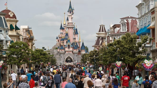 Visitors walk toward the Sleeping Beauty's Castle at Disneyland Paris in Chessy, France, east of Paris, on May 12, 2015.