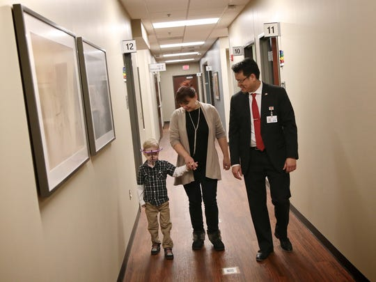 Dr. Kongkrit Chaiyaste, pediatric plastic surgeon at Beaumont hospital, walks with Denis Chubanyuk, 5, and his mother Elena Chubanyuk during a check up visit at Beaumont hospital on Wednesday, February 3, 2016, in Royal Oak, MI. Denis is being treated for a rare condition that caused his eyes to bulge, head and face to appear misshapen.