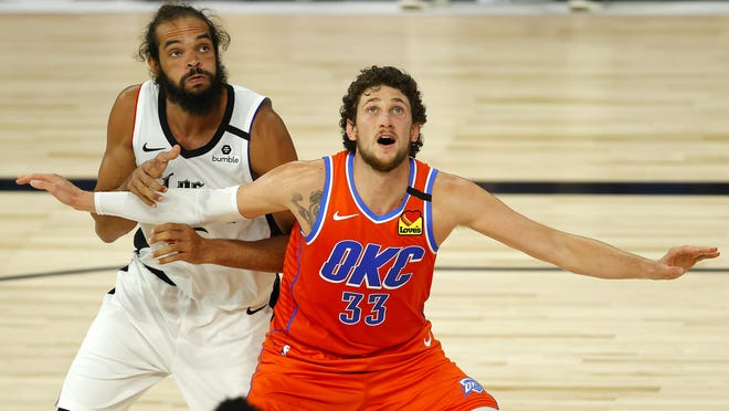 Mike Muscala of the Oklahoma City Thunder, center, and Joakim Noah of the LA Clippers battle for position during the third quarter at The Field House at ESPN Wide World Of Sports Complex on Aug. 14, 2020, in Lake Buena Vista, Florida.