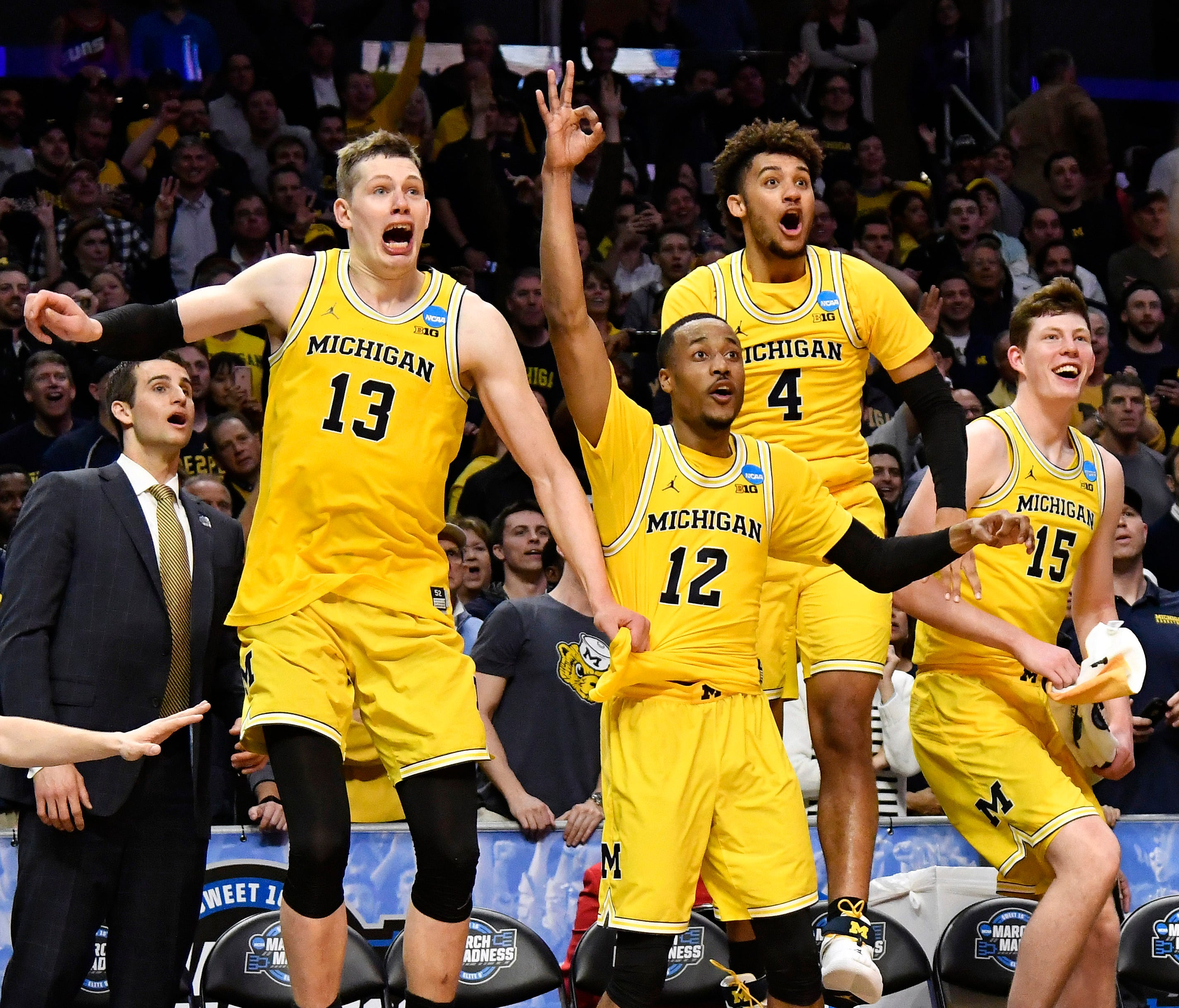 Michigan Wolverines forward Moritz Wagner (13) and guard Muhammad-Ali Abdur-Rahkman (12) and forward Isaiah Livers (4) and center Jon Teske (15) celebrate after defeating the Texas A&M Aggies in the semifinals of the West regional of the 2018 NCAA To
