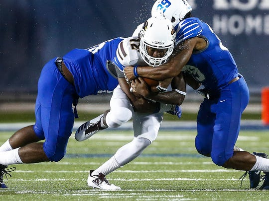 University of Memphis teammates Bryce Huff (left) and Christian Slaughter (right) bring down University of Louisiana-Monroe receiver Markis McCray (middle) during third quarter action at the Liberty Bowl Memorial Stadium.