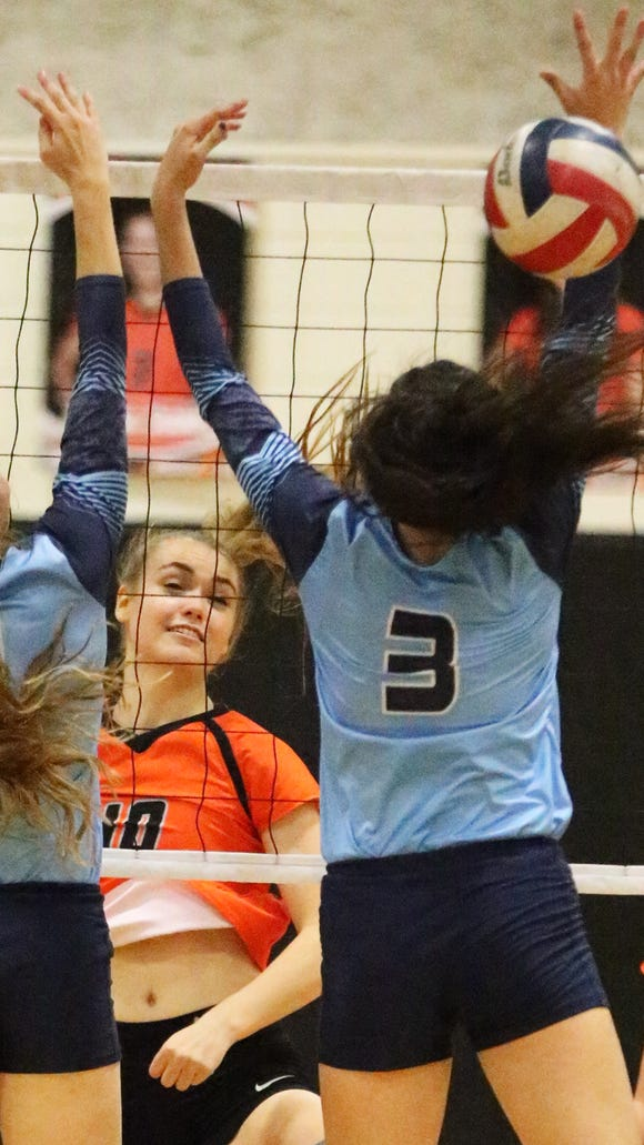 Jordan Rash, center, of El Paso High fires past the outstretched arms of Chapin's Amelia Crossley, left, and Jessica Landeros, 3, Tuesday night. The Tigers beat the Huskies in their home court after 5 sets.