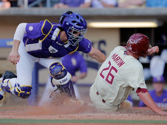 Florida State's Robby Martin (26) scores on a fielding error by LSU catcher Saul Garza, left, in the second inning of Game 2 of the NCAA college baseball super regional tournament in Baton Rouge, La., Sunday, June 9, 2019. (AP Photo/Gerald Herbert)
