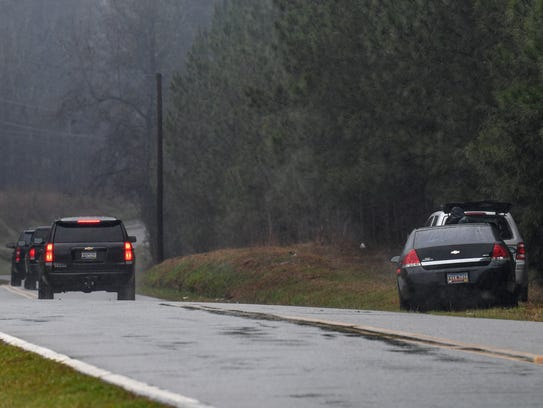 Cars with  tinted windows leave the corner of Little Mountain Road near Travis Road in Anderson on Tuesday. The FBI continued its investigation of suspicious packages, which have twice been found near where those roads intersect.