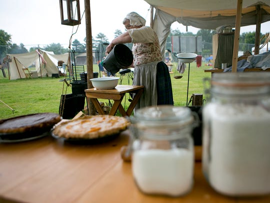 Pat Streich of Rothschild pours water into a bowl Saturday during the French and Indian trading camp demonstration at Greenwood Summer Fest. Streich was demonstrating how to cook using methods from the 1800s.