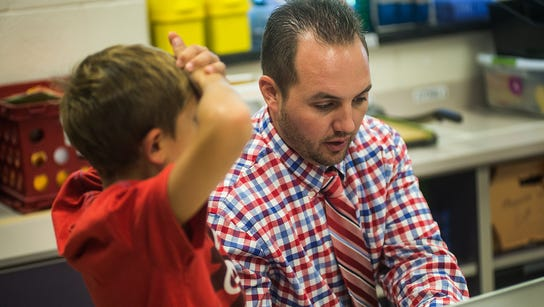 Fourth-grade teacher Ben Olewiler troubleshoots a student's