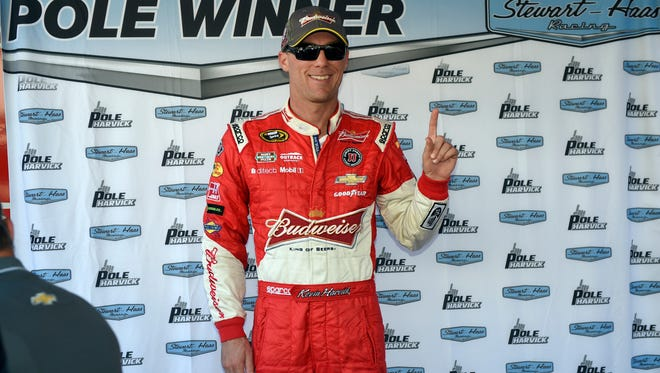 Driver Kevin Harvick poses outside his hauler after he won the pole position during qualifying for the NASCAR Sprint Cup series auto race, Friday, Sept. 26, 2014, at Dover International Speedway in Dover, Del. (AP Photo/Nick Wass)