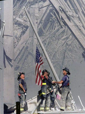**Brooklyn firefighters George Johnson, left, of ladder 157, Dan McWilliams, center, of ladder 157, and Billy Eisengrein, right, of Rescue 2, raise a flag at the World Trade Center in New York, in this Sept. 11, 2001, file photo, as work at the site continues after hijackers crashed two airliners into the center. In the most devastating terrorist onslaught ever waged against the United States, knife-wielding hijackers crashed two airliners into the World Trade Center, toppling its twin 110-story towers. This year will mark the fifth anniversary of the attacks.  (AP Photo/ Copyright 2001 The Record (Bergen County, NJ), Thomas E. Franklin, Staff Photographer/FILE)
