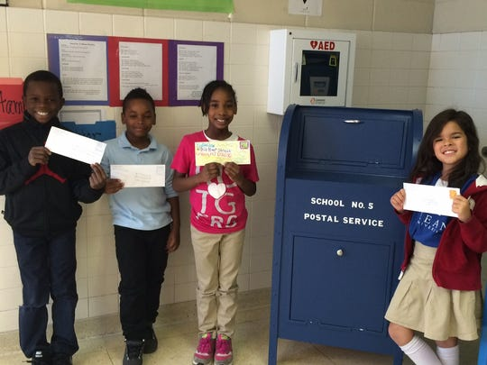 Third grade students from Roxy Suggs' class, Anwar Witherspoon, Jayden Halley, Kyla Daux, and Zeniah Rosario are mailing the letters they wrote thanking staff members for their services.