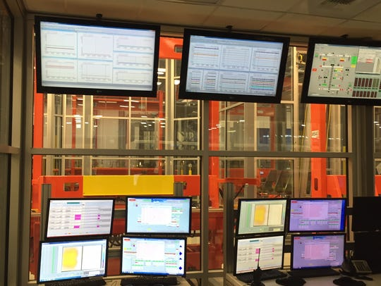A multi-screen control room monitors the automated