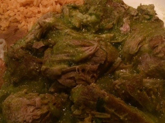 The pork carnitas are hunks of braised pork under a cloak of tangy tomatillo sauce, served with refried beans, red rice and tortillas.