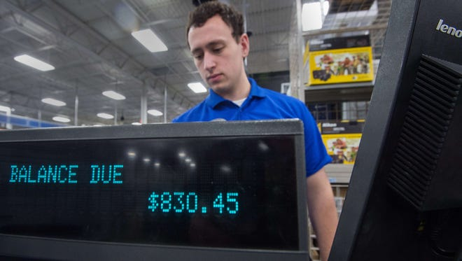 Holiday season sales fared better than 2013 as consumers spent more and shopped more often. Here, a salesperson rings up a purchase at a Best Buy in Fairfax, Va., on Thanksgiving, Nov. 27, 2014.